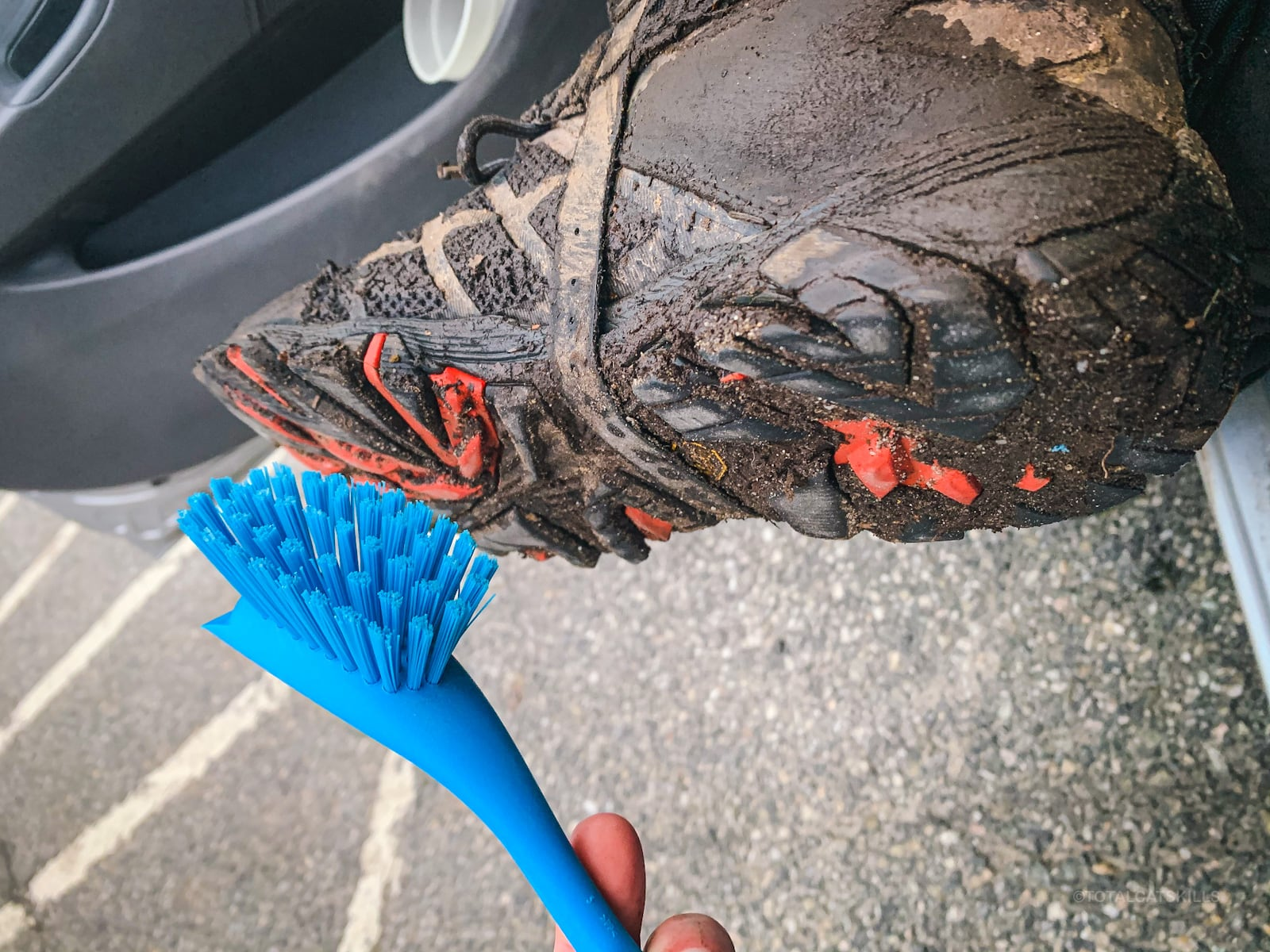 blue plastic brush cleaning dirt off bottom of dirty hiking hoot
