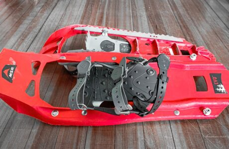 red snowshoes stacked on wooden floor