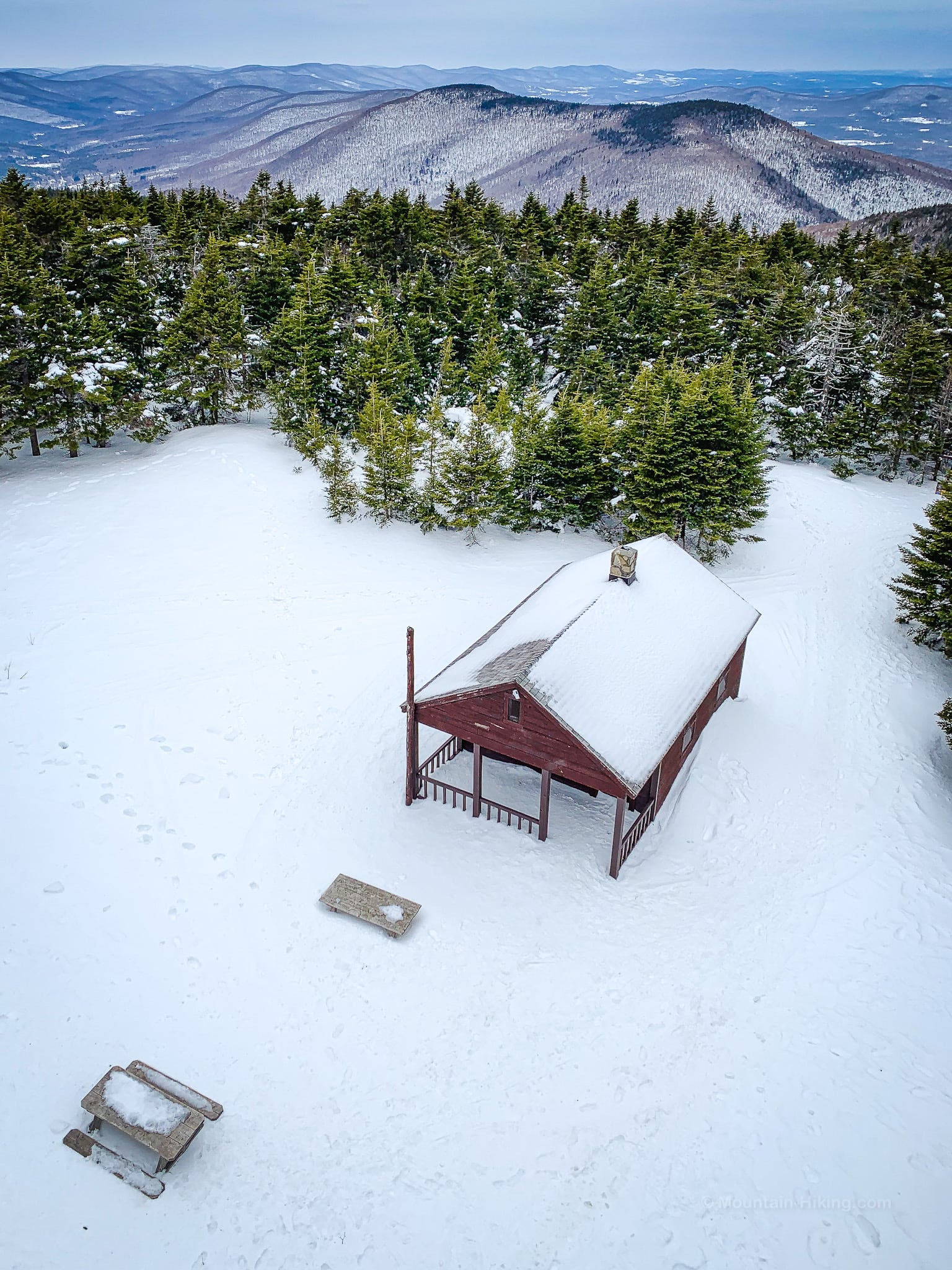 cabin and picnic tables in deep snow, mountains in distance