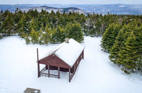 cabin in snow on mountain summit