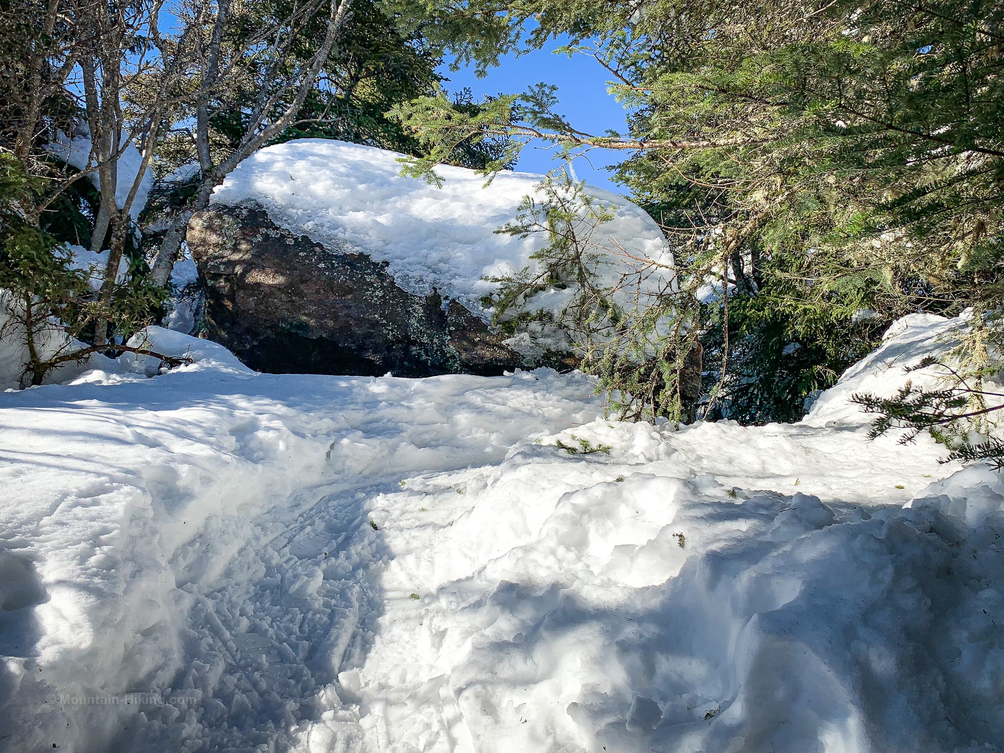boulder covered in snow on mountain summit