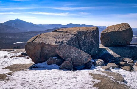 large glacial erratic boulders with mountain summits behind